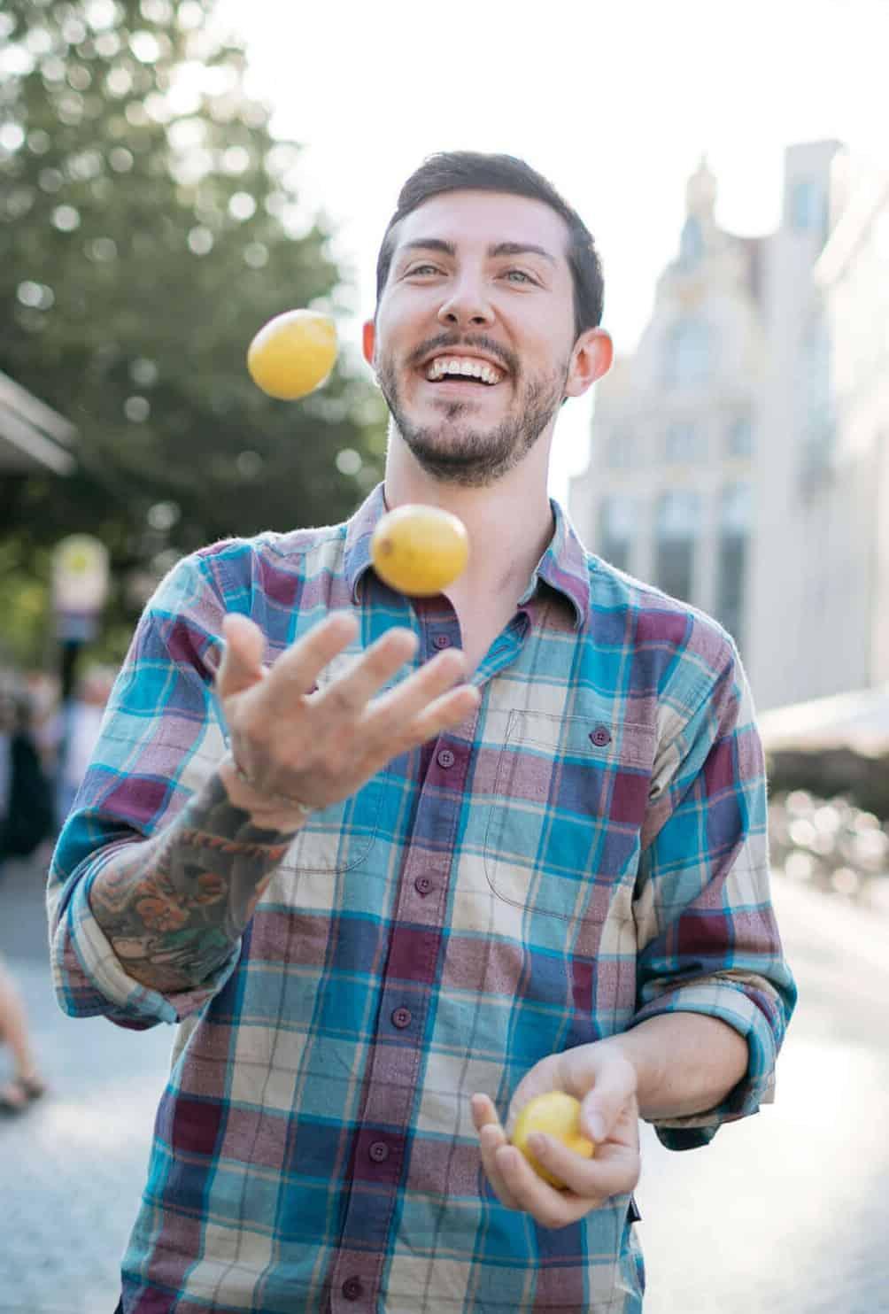 Junger Mann, der jongliert aus Tinder Fotoshooting